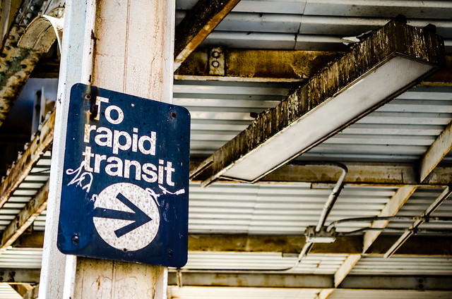 "In the foreground, the photo depicts a rusted sign with ""To rapid transit"" and an arrow. The sign is marked with tagging-style graffiti. In the background are rusted iron girders, part of the infrastructure of the L train."